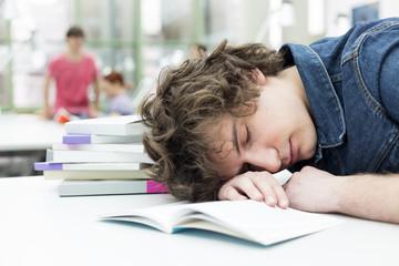 Studenten schlafen erschöpft in einer Universitätsbibliothek