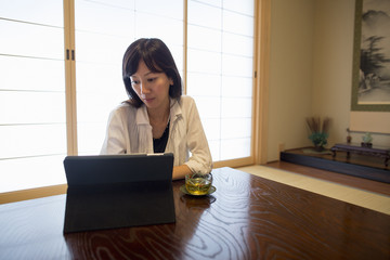 A woman sitting at a table with a laptop computer.