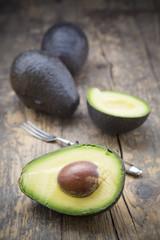 Scheiben und ganze Avocados (Persea Americana) auf Holztisch