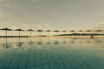 Kroatien, Sibenik, Sonnenschirme, Pool von einer Hotelanlage, Abendstimmung