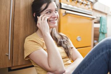 Lächelnde junge Frau Frau beim Telefonieren in ihrer Küche