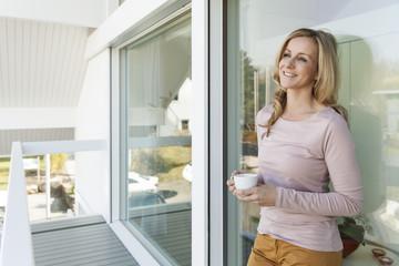 Frau mit einer Tasse Kaffee lehnt an Scheibe vor ihrem Haus