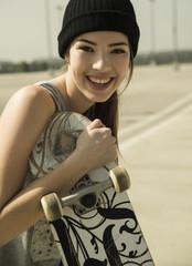 Lächelnde junge Frau Frau mit Skateboard
