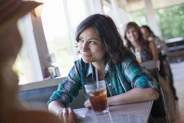 A woman seated at a diner looking out of the window.