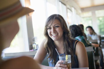 A woman sitting at a diner table holding a cool drink.