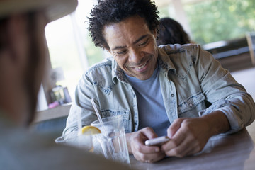 A man checking his smart phone at a diner table.
