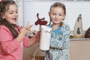 Portrait von zwei kleinen Mädchen mit Handrührgerät in der Küche