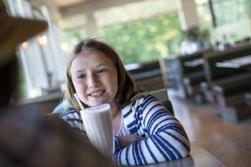 A young girl with a large milk shake at a diner table.
