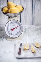 Zitronen auf Küchenwaage und Zitrone in Scheiben geschnitten