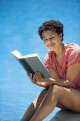 A woman sitting at a swimming pool, reading a book.