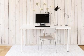 Büro zu Hause mit PC, Headset und Haftnotizen an der Wand