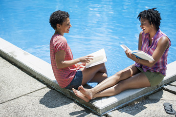 Two women sitting by the side of a swimming pool, reading books.