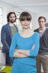 Junge Frau mit ihren zwei Kollegen im Hintergrund, im Büro