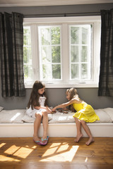 Two girls playing together indoors.