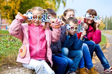 Дети держат логотип гугл в руках у лица