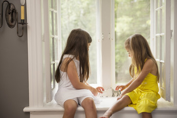 Two girls playing together, sitting on a window seat indoors.