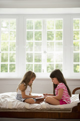 Two girls sitting and playing, using a digital tablet.