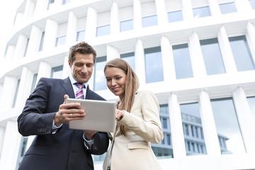 Geschäftsmann und Geschäftsfrau mit Tablet-Computer, vor Hotel