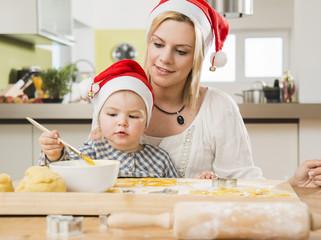 Mutter und Tochter tragenWeihnachtsmützen, Backen in der Küche