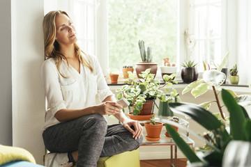 Junge Frau mit Handy in der Hand sitzt und träumt zwischen ihren Pflanzen