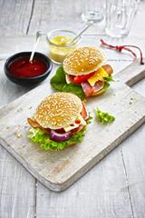 Zwei vorbereitete Burger, Senf und Ketchup auf hölzernen Boden