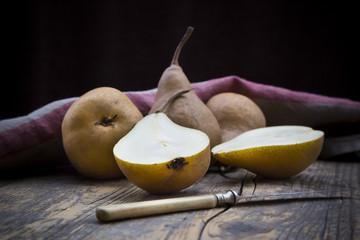 Geschnittene und ganze Birnen (Pyrus), ein Messer und eine Küchentuch