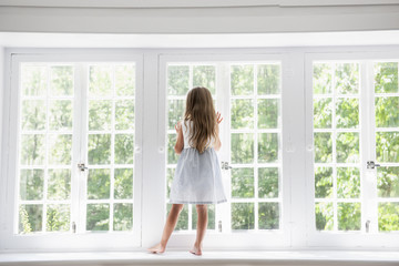 A child standing at a window looking out.