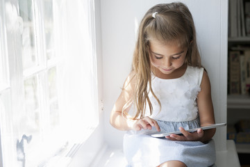 A young girl sitting at a window seat, using a digital tablet.