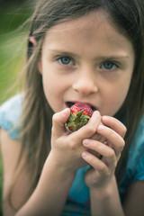 Portrait des kleinen Mädchens, das Erdbeere isst