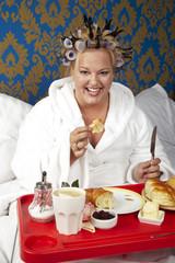 Porträt einer Frau mit Lockenwicklern und weißen Bademantel mit einem Frühstück im Bett