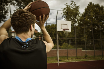 Junger Basketballspieler strebt zum Basketballkorb, Blick zurück