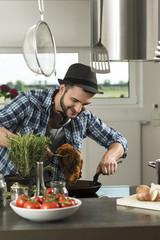 Junger Mann in der Küche kocht zu Hause