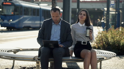 Business people working on laptop and drinking coffee on bench i