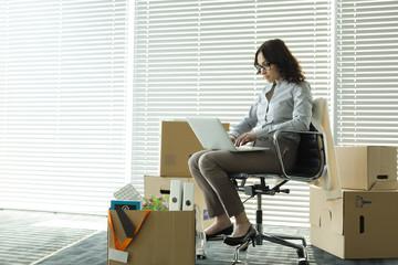 Geschäftsfrau mit Laptop auf leerer Büroetage mit Kartons