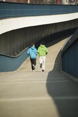 Junger Mann und Teenager auf der Brücke laufend