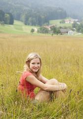 Österreich, Salzkammergut, Mondsee, junge Frau sitzt auf einer Wiese