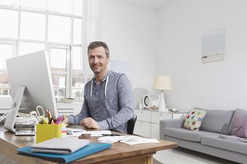 Man sitzt zu Hause am Schreibtisch mit Computer