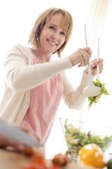 lächelnden reifen Frau mit Salatbesteck