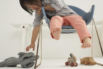 Kleines asiatisches Mädchen sitzt auf einem Stuhl, greift ihr Kuscheltier