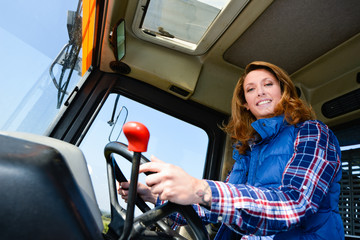 cheerful young woman farmer driving tractor in the fields