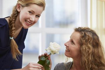 Tochter präsentiert ihrer Mutter eine weiße Rose