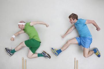 Zwei Männer springen über Hürden