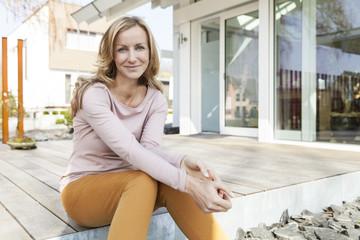 Frau sitzt auf der Terrasse des Wohnhauses