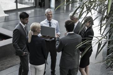 Gruppe von Geschäftsleuten mit Laptop in der Lobby