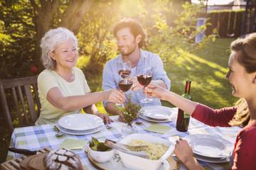 Paar und ältere Frau, beim Abendessen im Garten