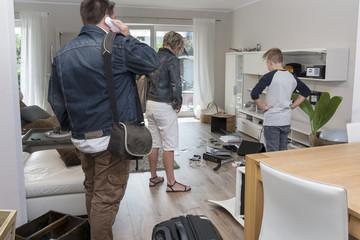 Familie steht vor dem Chaos nach Einbruch, Rückkehr ins Einfamilienhaus nach Urlaub