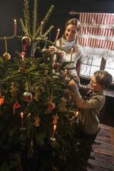 Mutter und ihr kleiner Sohn entzünden Kerzen eines Weihnachtsbaumes in einem Bauernhaus