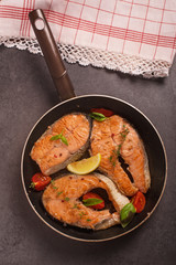 Fried salmon seak in pan with lemonq tomatto and aromatic herbs