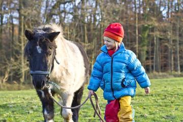 Kleines Mädchen mit Pony auf einer Wiese