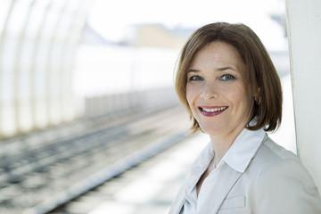 Geschäftsfrau wartet auf Bahnsteig